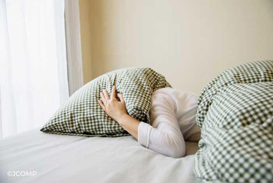 Frau im Bett mit Polster über dem Kopf