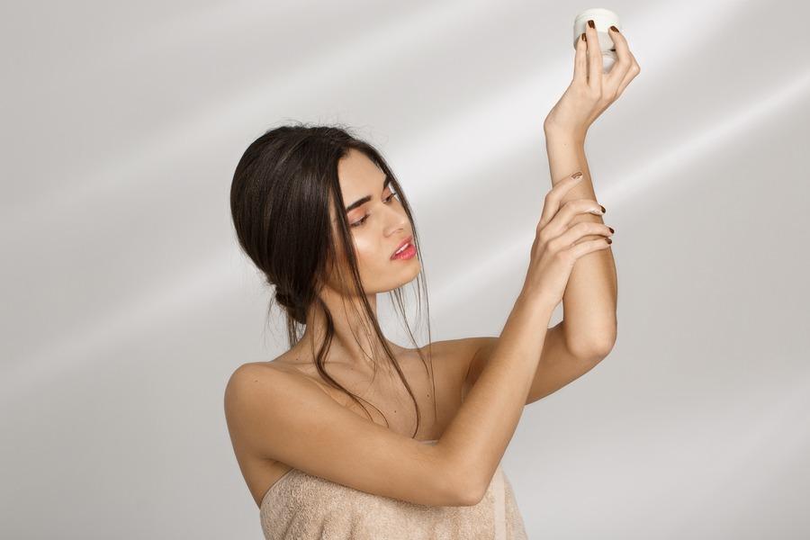 Frau cremt sich trockene Haut ein