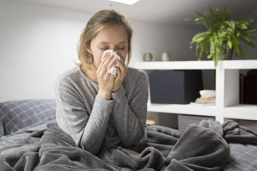 kranke Frau sitzt im Bett und schnäuzt sich